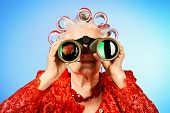 foto of hair curlers  - Portrait of an elderly woman in curlers looking ahead through binoculars - JPG