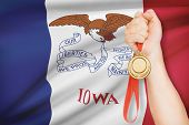 Medal In Hand With Flag On Background - State Of Iowa. Part Of A Series.