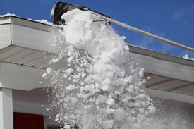image of soffit  - Raking snow on the roof in winter time - JPG