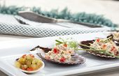 stock photo of scallop-shell  - A close up of tuna salad mixed with diced red bell pepper and topped with chives served on scallop shells with a side of freshly diced relish - JPG