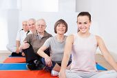 stock photo of senior class  - Portrait of smiling trainer and senior customers sitting together in yoga class - JPG