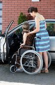 stock photo of independent woman  - Young girl assisting senior disabled woman getting into a car - JPG