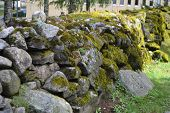 picture of old stone fence  - Old stone fence covered with moss Lappeenranta Finland - JPG