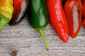 pic of jalapeno  - Border of Red and Green Habanero and Jalapeno Chili Peppers isolated on Rustic Wooden background - JPG