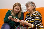 stock photo of knitted cap  - Young and old knitting and crocheting together - JPG