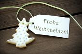 picture of weihnachten  - A Christmas Tree Cookie with a Label with the German Words Frohe Weihnachten on it which means Merry Christmas