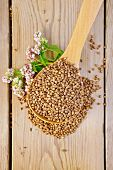 image of buckwheat  - Buckwheat in a spoon with flower buckwheat on a wooden boards background - JPG