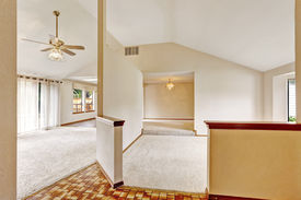 stock photo of linoleum  - Bright empty house interor with entrance hallway. Brown linoleum floor blend with wooden trim. View of rooms with vaulted ceiling and carpet floor ** Note: Soft Focus at 100%, best at smaller sizes - JPG