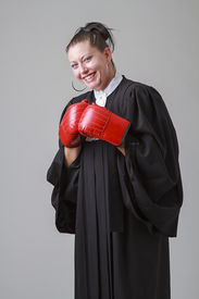 picture of toga  - woman in her thirties wearing a black toga canadian lawyer toga and red boxing gloves laughing at the thought of fighting - JPG