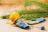 stock photo of pine-needle  - ball of threads knitting needles mittens and branch of pine on wooden background - JPG