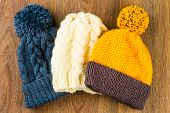foto of knitted cap  - yellow white and gray knitting caps on wooden background - JPG