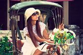 image of riding-crop  - Young white woman sitting in rickshaw with bunch of flowers and looking away - JPG