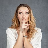 picture of hush  - Attractive young woman with finger on lips concept of student show quiet silence secret gesture hush - JPG