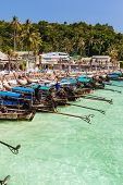 stock photo of phi phi  - the main pier of the tropical thai island named Phi Phi with a lot of colorful longtail boats - JPG