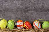 stock photo of egg whites  - Colorful easter eggs on aged wooden background - JPG