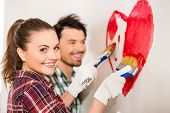stock photo of wall painting  - Young happy couple are painting a heart on the wall while doing repair at home - JPG