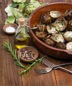 stock photo of artichoke hearts  - Artichokes cooked with olive oil on a wooden table - JPG