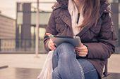 stock photo of ordinary woman  - Detail of a young woman working with her tablet in the city streets - JPG