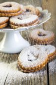 picture of linzer  - Linzer cookies sprinkled with powdered sugar on a wooden table - JPG