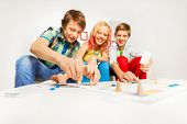 stock photo of indoor games  - Girl and two boys playing table game sitting on white sofa and table at home - JPG