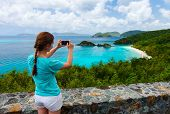 Постер, плакат: Back view of tourist girl taking photo with mobile cell phone of Trunk bay on St John island US Vir