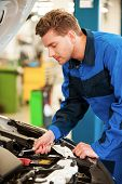 pic of concentration man  - Concentrated young man in uniform repairing car while standing in workshop - JPG