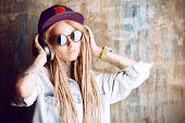 picture of dreadlock  - Trendy teenage girl with blonde dreadlocks listening to music on headphones - JPG