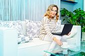 stock photo of sofa  - Smiling elegant woman sitting on a sofa with her laptop computer - JPG