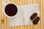 stock photo of eclairs  - Mini Eclairs with a cup of tea on a background paper for information - JPG