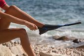 foto of flipper  - Sexy girl on the beach puts on her flipper - JPG