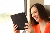 foto of passenger train  - Happy passenger woman reading a tablet or ebook traveling inside a train - JPG