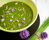 picture of edible  - Swiss chard and potato cream soup with chopped chives with edible chives flowers in green ceramic bowl - JPG