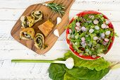 stock photo of rocket salad  - Dough rolls strudel with swiss chard and chorizo on chopping board young garlic with lettuce and rocket leaves salad chopped radishes white painted wood background - JPG