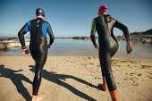 picture of triathlon  - Rear view of triathlon participants ready to start of the race - JPG