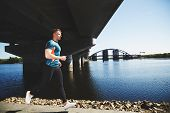 picture of leggins  - Young handsome man running along the embankment near the river under the bridge