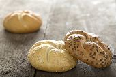 stock photo of bagel  - Close up of a sesame seed bagel and others with seeds over wooden background - JPG