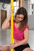 picture of pole dancer  - Young beauty pole dancer sitting on the floor - JPG