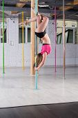 image of pole dancer  - Young beauty pole dancer doing advanced figure - JPG