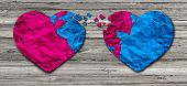 image of two hearts  - Romantic relationship concept as two hearts made of torn crumpled paper on weathered wood as a symbol for romance attachment and exchange of feelings and emotions of love - JPG