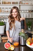 stock photo of juicer  - Beautiful happy woman making healthy diet juice with juicer - JPG