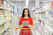 picture of department store  - Young girl in a market store with a PC tablet in a department store - JPG
