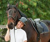 stock photo of horse-breeding  - Cheerful young jockey woman with purebred horse outdoors - JPG