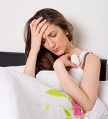 image of suffering  - young woman suffering from a migraine holding pills - JPG