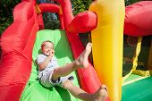 picture of inflatable slide  - Small boy jumping down the slide on an inflatable bouncy castle - JPG