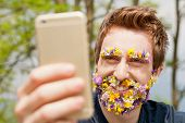 image of take responsibility  - hipster man with flowers instead of his beard and eyebrows texting with his mobile phone - JPG