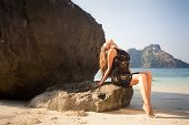 foto of barefoot  - young brunette girl in black transparent lace dress sits on stone barefoot against sea and islands - JPG