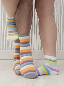 image of stocking-foot  - feet of a beautiful couple with striped socks - JPG