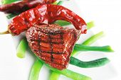 picture of veal  - served grilled beef veal fillet entrecote on a white plate with peppers and green peas on long plate isolated on white background - JPG