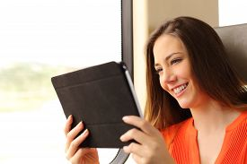picture of passenger train  - Happy passenger woman reading a tablet or ebook traveling inside a train - JPG