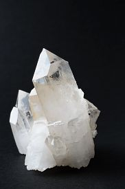 stock photo of cluster  - A quartz crystal cluster against a black background - JPG